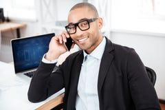 Νέος επιχειρηματίας που μιλά στο κινητό τηλέφωνο και που εξετάζει τη κάμερα Στοκ Φωτογραφία