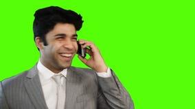 Νέος επιχειρηματίας που μιλά στο κινητό τηλέφωνο στο πράσινο κλίμα απόθεμα βίντεο