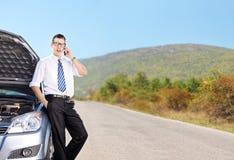 Νέος επιχειρηματίας που μιλά στο τηλέφωνο δίπλα σε ένα αυτοκίνητο Στοκ φωτογραφία με δικαίωμα ελεύθερης χρήσης