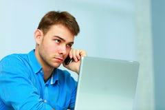 Νέος επιχειρηματίας που μιλά στο τηλέφωνο και που εξετάζει το copyspace Στοκ Φωτογραφία