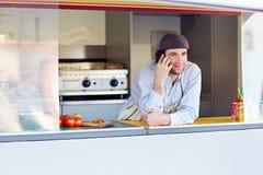 Νέος επιχειρηματίας που μιλά στο τηλέφωνο στα take-$l*away τρόφιμά του stal Στοκ Φωτογραφία