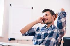 Νέος επιχειρηματίας που μιλά στο τηλέφωνο στην αρχή Στοκ εικόνα με δικαίωμα ελεύθερης χρήσης