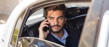 Νέος επιχειρηματίας που μιλά στο τηλέφωνο στη λιμουζίνα Στοκ Φωτογραφίες