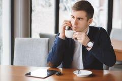 Νέος επιχειρηματίας που μιλά στο τηλέφωνο στον καφέ Στοκ Φωτογραφία