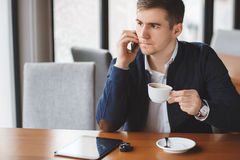Νέος επιχειρηματίας που μιλά στο τηλέφωνο στον καφέ Στοκ εικόνα με δικαίωμα ελεύθερης χρήσης