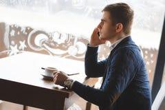 Νέος επιχειρηματίας που μιλά στο τηλέφωνο στον καφέ Στοκ Φωτογραφίες