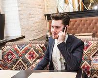 Νέος επιχειρηματίας που μιλά στο τηλέφωνο στο εσωτερικό Στοκ Εικόνα