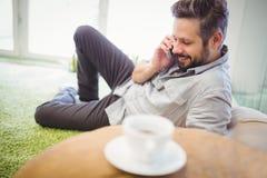 Νέος επιχειρηματίας που μιλά στο τηλέφωνο στο δημιουργικό γραφείο Στοκ Φωτογραφίες