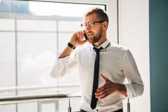 Νέος επιχειρηματίας που μιλά στο τηλέφωνο στο λόμπι του γραφείου Στοκ φωτογραφία με δικαίωμα ελεύθερης χρήσης