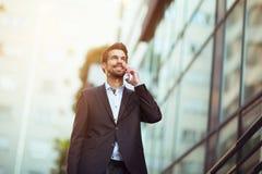 Νέος επιχειρηματίας που μιλά στο τηλέφωνό του υπαίθρια Στοκ Εικόνες