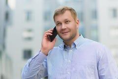 Νέος επιχειρηματίας που μιλά στο τηλέφωνό του υπαίθρια Στοκ εικόνα με δικαίωμα ελεύθερης χρήσης