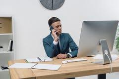 Νέος επιχειρηματίας που μιλά στο smartphone καθμένος στον πίνακα γραφείων με τον υπολογιστή γραφείου Στοκ φωτογραφία με δικαίωμα ελεύθερης χρήσης