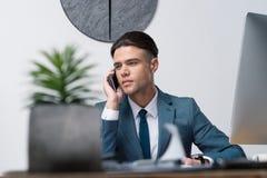 Νέος επιχειρηματίας που μιλά στο smartphone και που φαίνεται μακριά στην αρχή Στοκ Φωτογραφία