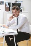 Νέος επιχειρηματίας που μιλά στο smartphone στην αρχή. Στοκ Εικόνα