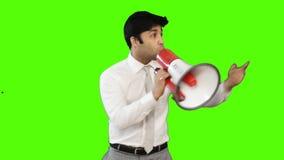 Νέος επιχειρηματίας που μιλά megaphone στο πράσινο υπόβαθρο φιλμ μικρού μήκους