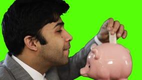 Νέος επιχειρηματίας που παρεμβάλλει τα χρήματα σε μια piggy τράπεζα στο πράσινο υπόβαθρο απόθεμα βίντεο