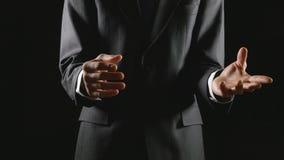 Νέος επιχειρηματίας που παρουσιάζει και που εξηγεί στο μαύρο υπόβαθρο φιλμ μικρού μήκους