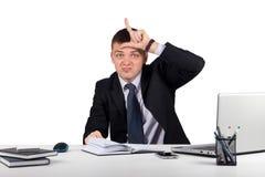 Νέος επιχειρηματίας που παρουσιάζει σημάδι ηττημένων στο μέτωπο, που εξετάζει σας που απομονώνεστε στο άσπρο υπόβαθρο Στοκ Εικόνα