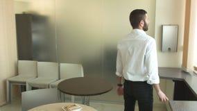 Νέος επιχειρηματίας που περπατά γύρω από την κουζίνα στο γραφείο φιλμ μικρού μήκους