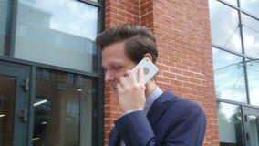 Νέος επιχειρηματίας που περπατά και που μιλά στο τηλέφωνο στο δρόμο του στο γραφείο απόθεμα βίντεο