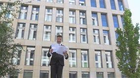 Νέος επιχειρηματίας που ρίχνει το έγγραφο με τα όπλα στον αέρα, σε αργή κίνηση φιλμ μικρού μήκους