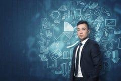 Νέος επιχειρηματίας που στέκεται μπροστά από το σκούρο μπλε τοίχο με τα διαφορετικά οικονομικά σκίτσα Στοκ φωτογραφία με δικαίωμα ελεύθερης χρήσης