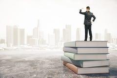 Νέος επιχειρηματίας που στέκεται σε έναν σωρό των βιβλίων και των βλεμμάτων μακριά Στοκ φωτογραφία με δικαίωμα ελεύθερης χρήσης