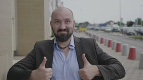 Νέος επιχειρηματίας που στέκεται στην οδό πόλεων που δίνει τους αντίχειρες που εκφράζουν επάνω την έγκριση και την υποστήριξη - απόθεμα βίντεο