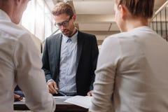 Νέος επιχειρηματίας που συζητά το νέο επιχειρηματικό σχέδιο με τους συναδέλφους Στοκ Εικόνα