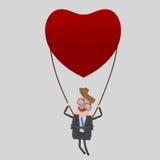 Νέος επιχειρηματίας που ταξιδεύει σε ένα μπαλόνι καρδιών Στοκ Εικόνα