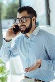 Νέος επιχειρηματίας που υποστηρίζει με το συνάδελφο στο τηλέφωνο Στοκ Φωτογραφίες