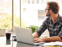 Νέος επιχειρηματίας που φαίνεται έξω το παράθυρο στη σκέψη Στοκ Εικόνες
