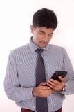 Νέος επιχειρηματίας που φαίνεται κινητό τηλέφωνο Στοκ εικόνες με δικαίωμα ελεύθερης χρήσης