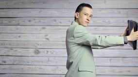 Νέος επιχειρηματίας που χορεύει και που περιστρέφει στα χέρια ενός χαρτοφυλακίου φιλμ μικρού μήκους