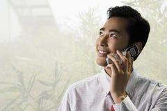 Νέος επιχειρηματίας που χρησιμοποιεί ένα κυψελοειδές τηλέφωνο Στοκ φωτογραφία με δικαίωμα ελεύθερης χρήσης