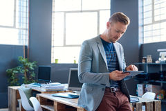 Νέος επιχειρηματίας που χρησιμοποιεί μια ταμπλέτα σε ένα γραφείο Στοκ Φωτογραφία