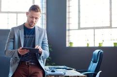 Νέος επιχειρηματίας που χρησιμοποιεί μια ταμπλέτα σε ένα γραφείο Στοκ Εικόνα
