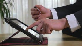 Νέος επιχειρηματίας που χρησιμοποιεί τις σε απευθείας σύνδεση τραπεζικές εργασίες σε ένα PC ταμπλετών απόθεμα βίντεο