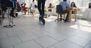 Νέος επιχειρηματίας που χρησιμοποιεί το ηλεκτρικό μηχανικό δίκυκλο που κινείται γύρω από το σύγχρονο καθιερώνον τη μόδα γραφείο Υ απόθεμα βίντεο