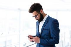 Νέος επιχειρηματίας που χρησιμοποιεί το κινητό τηλέφωνο στον εργασιακό χώρο στοκ φωτογραφία