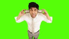 Νέος επιχειρηματίας που χρησιμοποιεί το τηλέφωνο δοχείων κασσίτερου στο πράσινο υπόβαθρο απόθεμα βίντεο