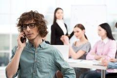Νέος επιχειρηματίας που χρησιμοποιεί το τηλέφωνο στην αρχή Στοκ Εικόνα