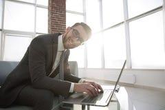Νέος επιχειρηματίας που χρησιμοποιεί το lap-top και το χαμόγελο Στοκ Εικόνες