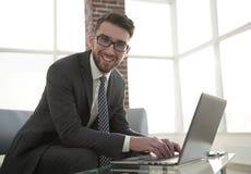 Νέος επιχειρηματίας που χρησιμοποιεί το lap-top και το χαμόγελο Στοκ φωτογραφίες με δικαίωμα ελεύθερης χρήσης