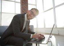 Νέος επιχειρηματίας που χρησιμοποιεί το lap-top και το χαμόγελο Στοκ φωτογραφία με δικαίωμα ελεύθερης χρήσης