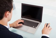 Νέος επιχειρηματίας που χρησιμοποιεί το lap-top στην αρχή Στοκ Φωτογραφίες