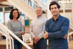Νέος επιχειρηματίας σε ένα γραφείο με τους συναδέλφους που στέκονται πίσω από τον Στοκ Εικόνα
