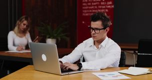Νέος επιχειρηματίας στα γυαλιά με την εργασία φορητών προσωπικών υπολογιστών και εγγράφου στην αρχή Επιχείρηση, άνθρωποι, γραφική απόθεμα βίντεο
