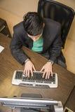 Νέος επιχειρηματίας στο γραφείο γραφείων που χρησιμοποιεί τον υπολογιστή Στοκ εικόνα με δικαίωμα ελεύθερης χρήσης