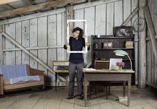 Νέος επιχειρηματίας στο γραφείο με το πλαίσιο παραθύρων στα χέρια Στοκ Εικόνες